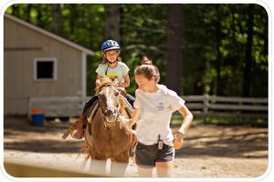 A counselor leads a young girl on a walk around our riding ring.