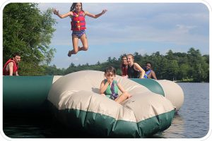 A camper leaps into the air to send a color-wars teammate flying off our water trampoline's blob.